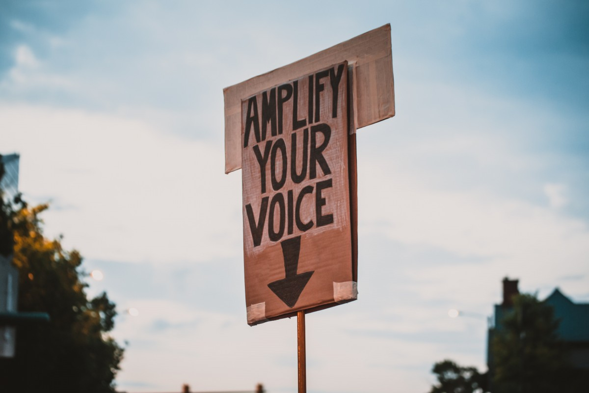 A wooden sign against the sky. Black text on the sign reads 'Amplify your voice' with an arrow pointing down