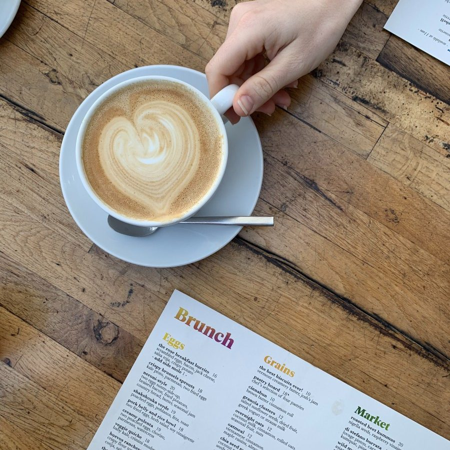 A hand holds a cup of coffee placed on a wooden table. Part of a brunch menu is visible